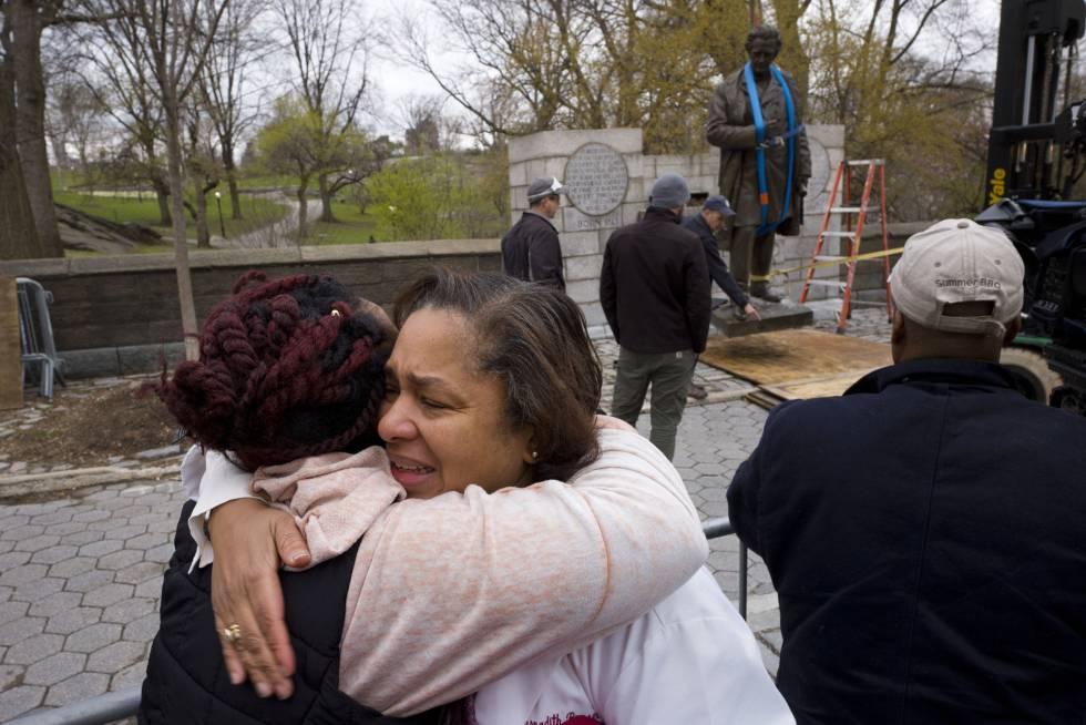 Dos mujeres se abrazan mientras funcionarios retiran la estatua del doctor J. Marion Sims de Central Park, el martes 17 de abril.