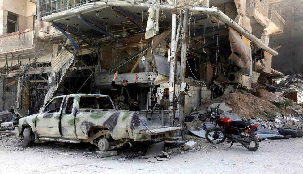 Soldados sirios, este viernes junto a un edificio en ruinas en Duma (Siria).