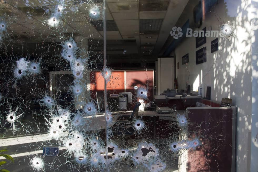 Impactos de armas de alto calibre en una sucursal bancaria que habría quedado atrapada en un tiroteo.