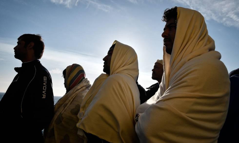 Migrantes rescatados frente a Libia en ruta a Italia observan la costa de Sicilia, el 10 de mayo.