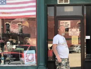 Jim Tracy a la entrada de una tienda en Winterset.