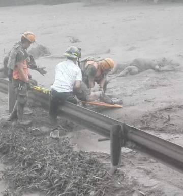 Trabalhos de resgate baixo a chuva de cinza em Guatemala, neste domingo.