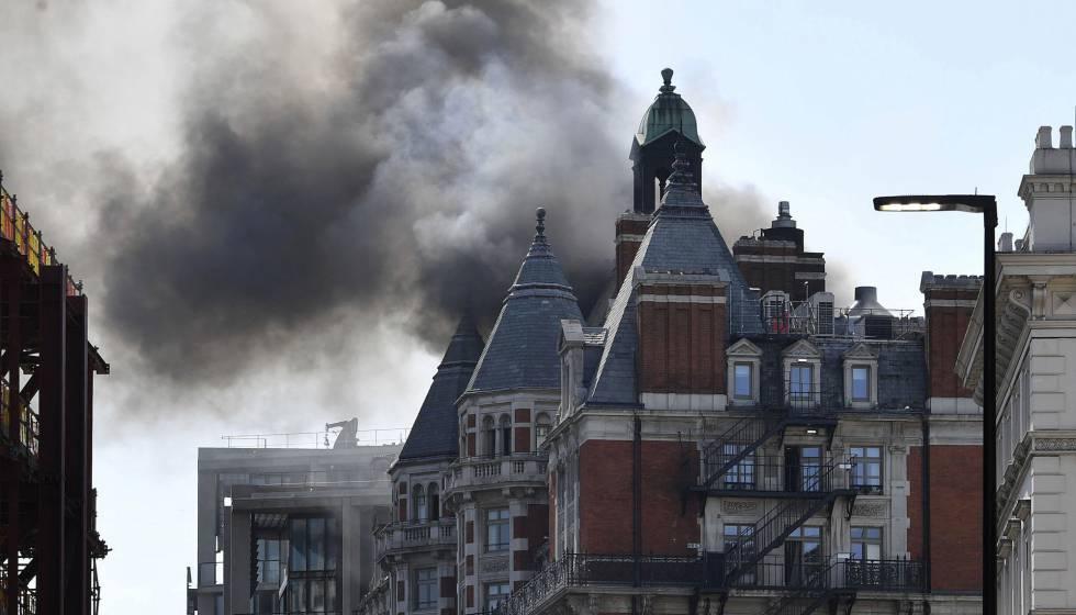 Una columna de humo se eleva sobre el edificio afectado por un incendio en el barrio de Knightsbridge, en Londres, este miércoles.