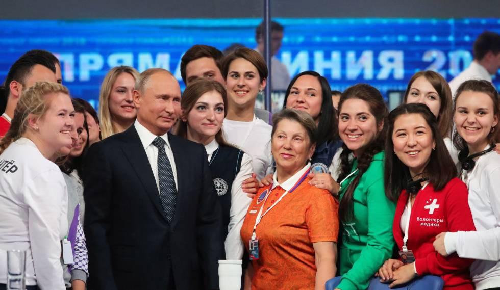 El presidente ruso, Vladímir Putin, posa con un grupo de voluntarios tras su programa nacional en directo.