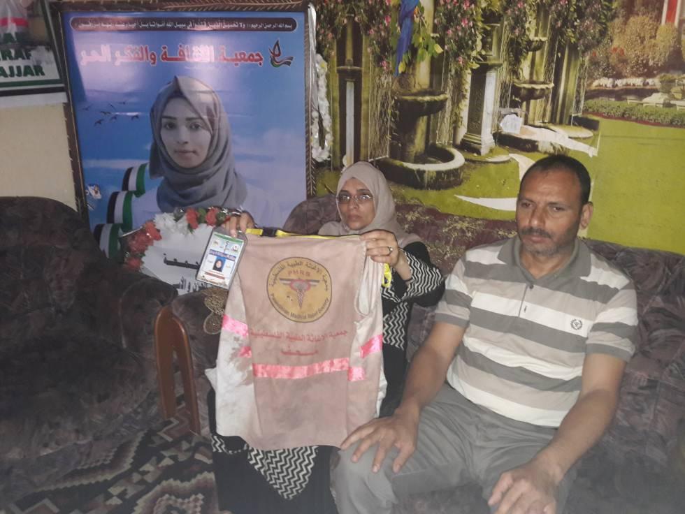 Los padres de la sanitaria palestina abatida el día 1 de junio en Gaza muestran su identificación como socorrista..