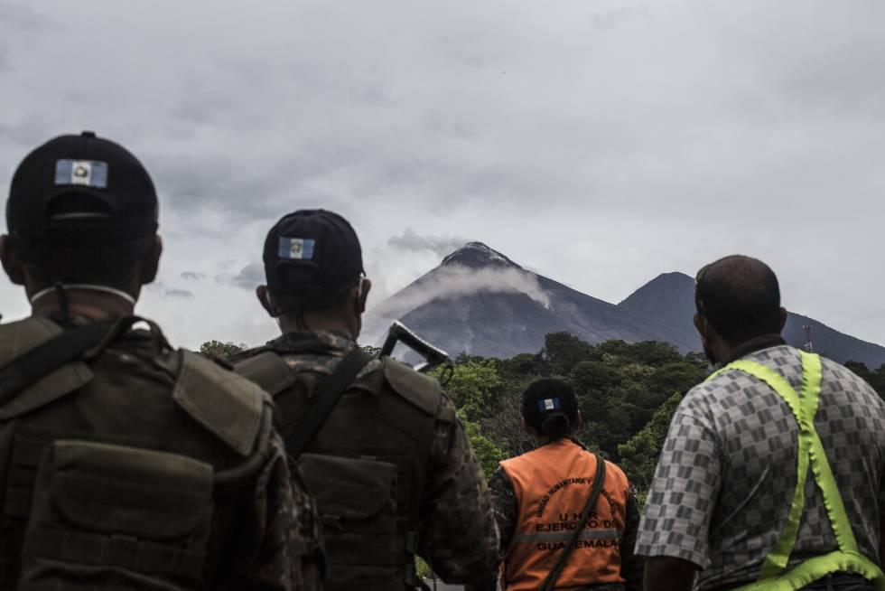 Elementos del ejército y rescatistas observan el volcán de Fuego tras una de sus exhalaciones, hasta el momento continua la alerta permanente.