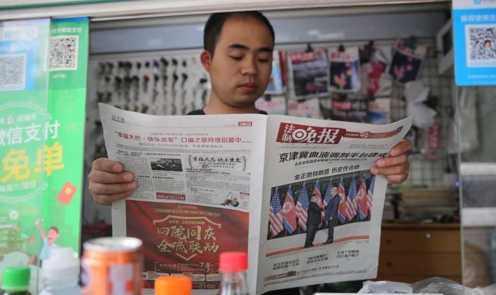 Un ciudadano chino lee un periódico que lleva a su portada una foto de la cumbre entre Trump y Kim.