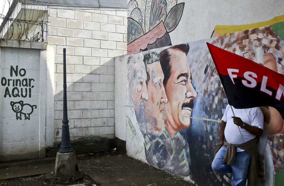 Un partidario de Ortega sostiene una bandera del partido sandinista FSLN apoyado en un mural el 26 de mayo.