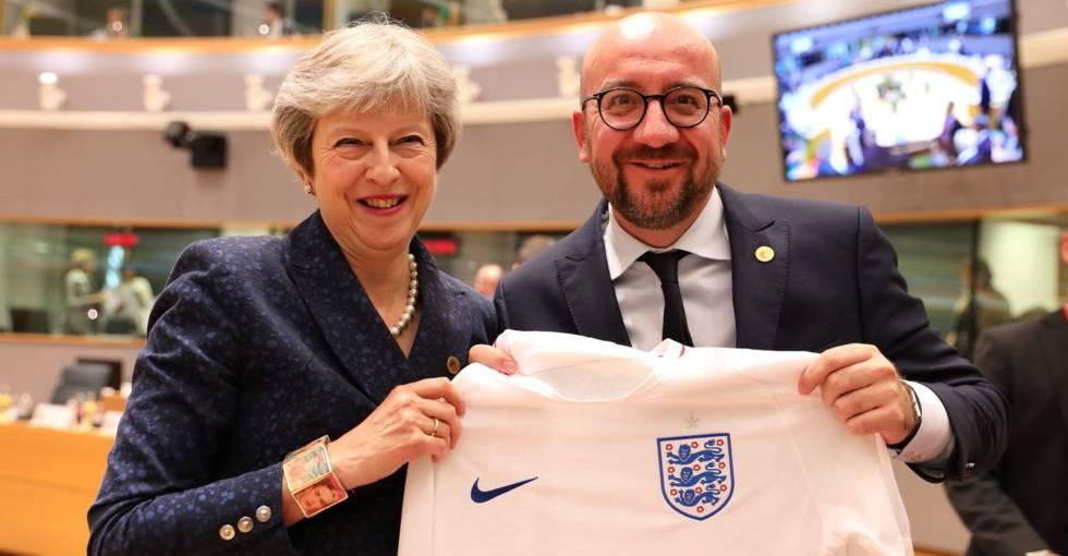 El primer ministro belga, Charles Michel, recibe de Theresa May la camiseta de la selección inglesa en la cumbre europea.