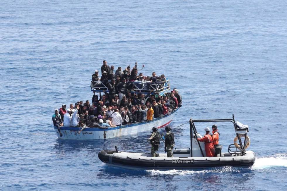 El equipo de salvamento aborda una barcaza con migrantes para rescatarlos.