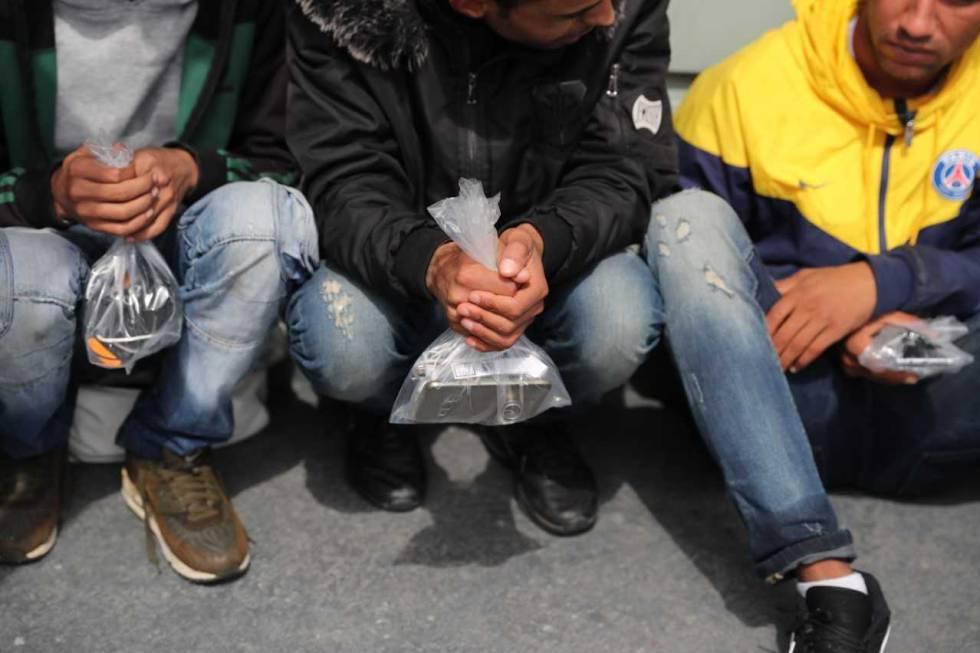 Migrantes recién rescatados, con sus pertenencias en una bolsa.