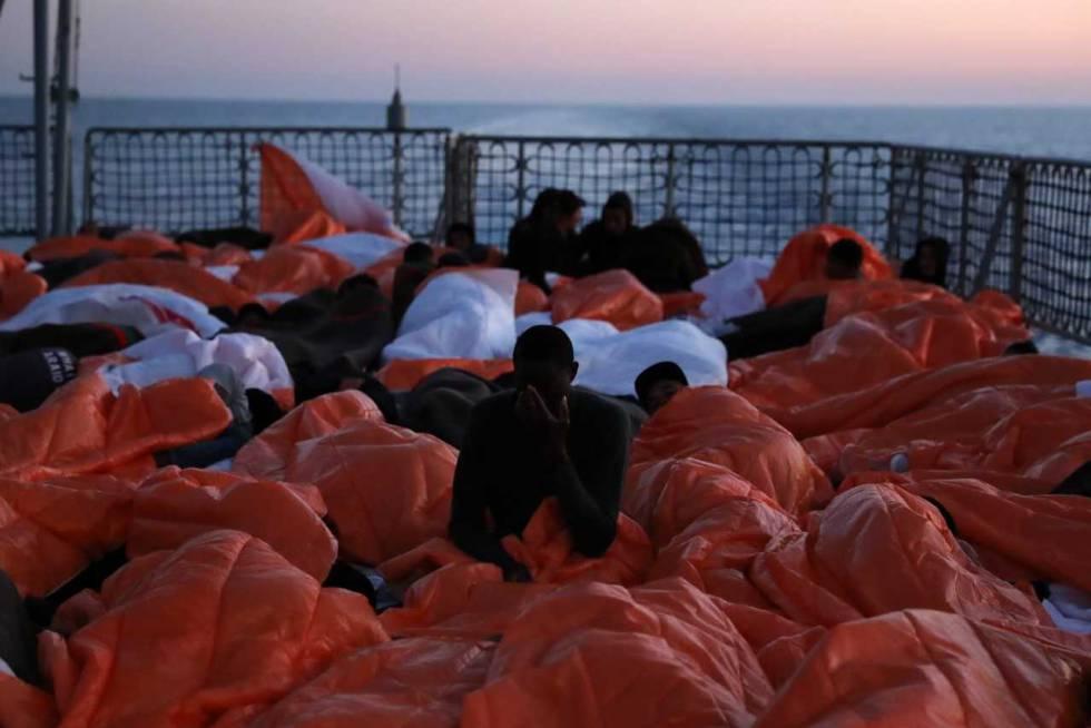 Migrantes tapados con mantas se disponen a pasar la noche en cubierta.