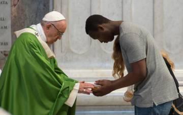 Um imigrante agradece o Papa na missa realizada na sexta-feira na basílica de São Pedro.