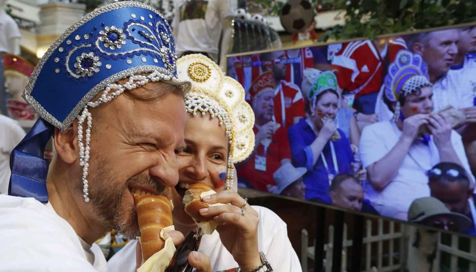 Dos personas posan para una foto junto a una pantalla que muestra a seguidores de España.
