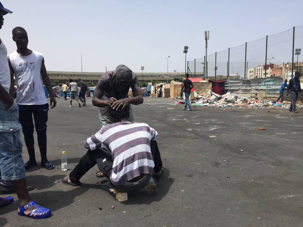 Un migrante corta el cabello a un compañero en el campamento de Casablanca.
