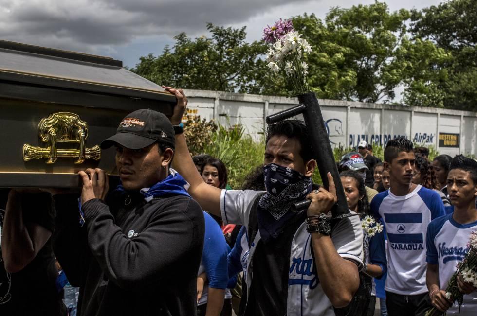 Un grupo de jóvenes carga el ataúd de Gerald Vásquez camino al cementerio.