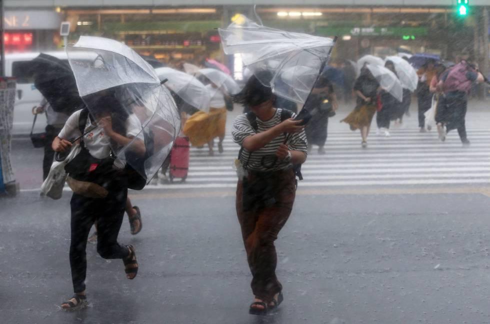 Peatones cruzando un paso entre lluvia y viento en Tokio, este sábado.