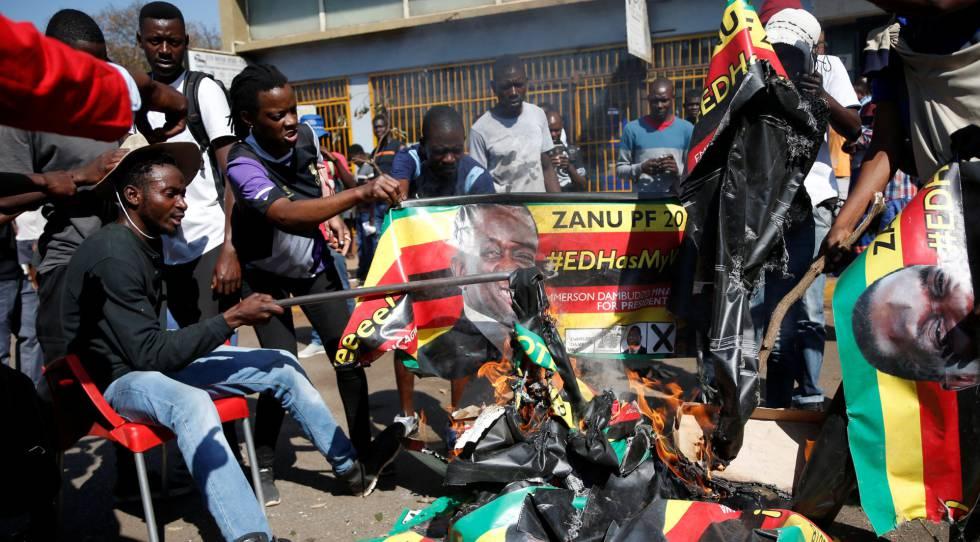 Simpatizantes del Movimiento para el Cambio Democrático (MDC) queman pancartas con la cara del presidente del país, Emmerson Mnangagwa, este lunes en Zimbabue.