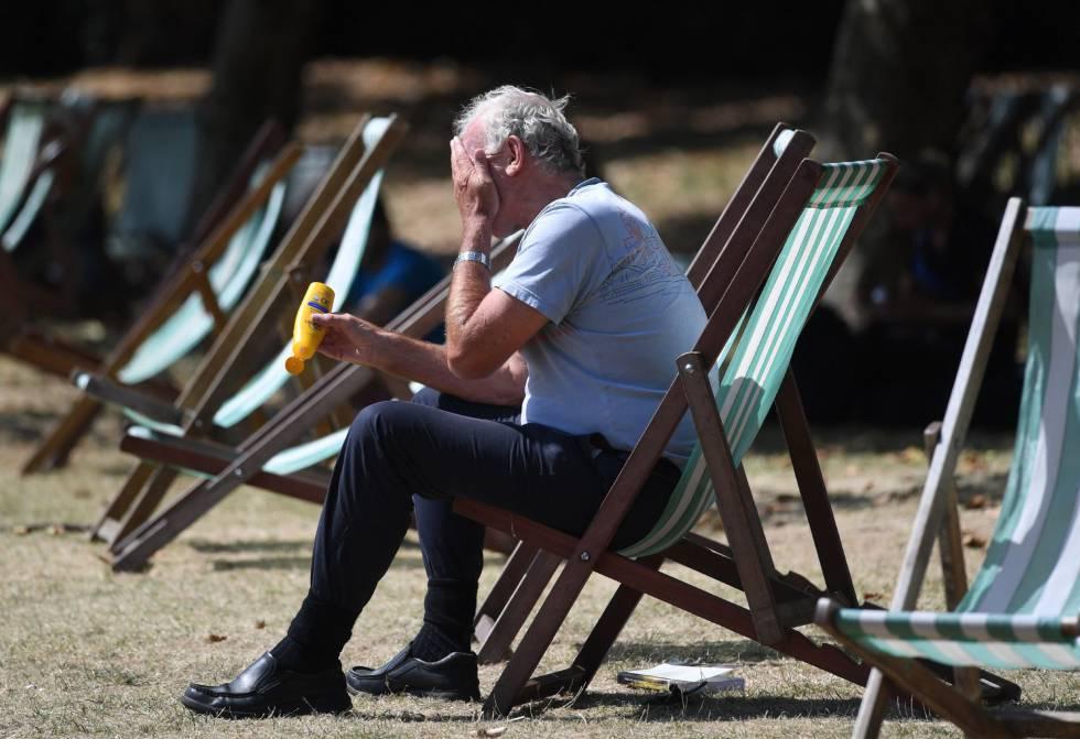 Un hombre se pone crema solar en el Green Park de Londres, Reino Unido.