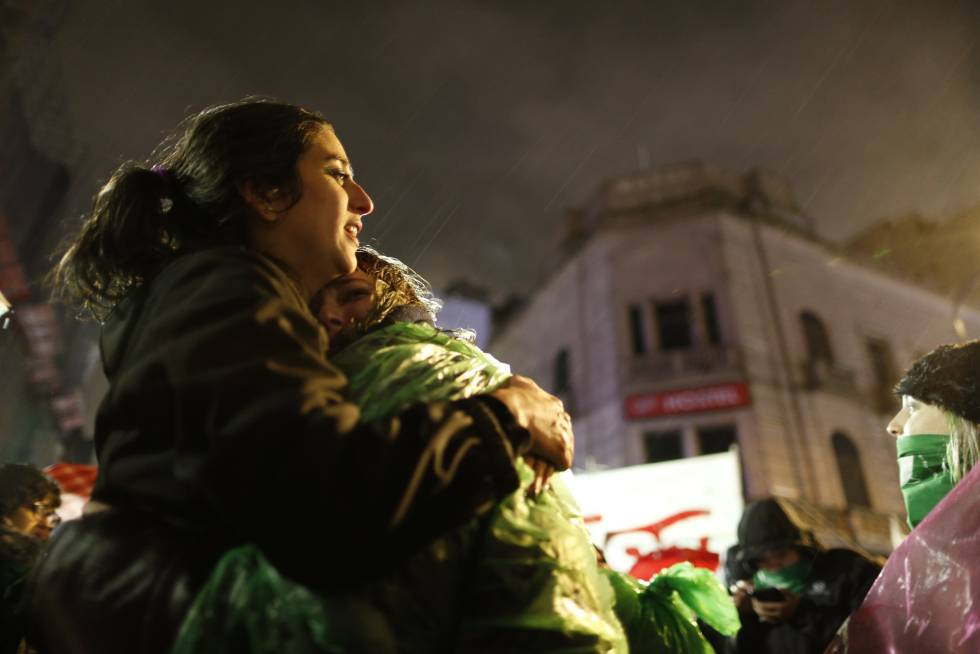 Dos jóvenes favorables al aborto legal se abrazan y lloran bajo la lluvia frente al Congreso argentino,