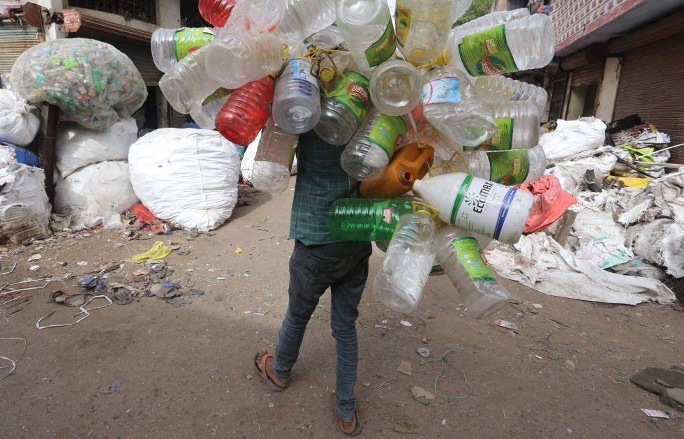 Un trapero carga a su espalda con botellas y bidones de plástico en las calles de la ciudad india de Bhopal, el pasado junio.