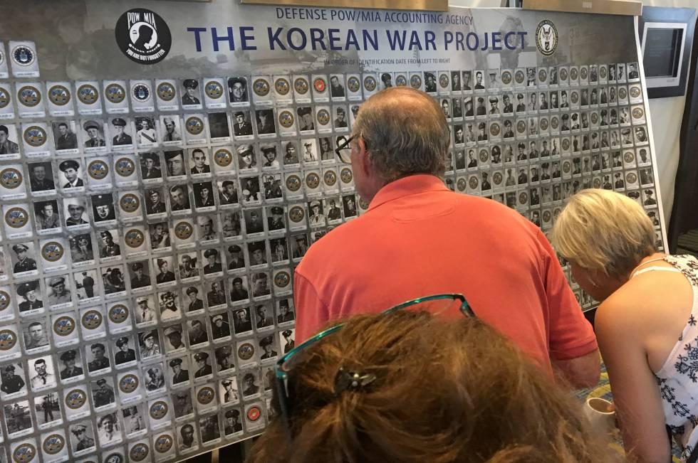 Varios familiares de soldados desaparecidos en la guerra de Corea miran un panel con información durante un evento en Arlington, el 9 de agosto