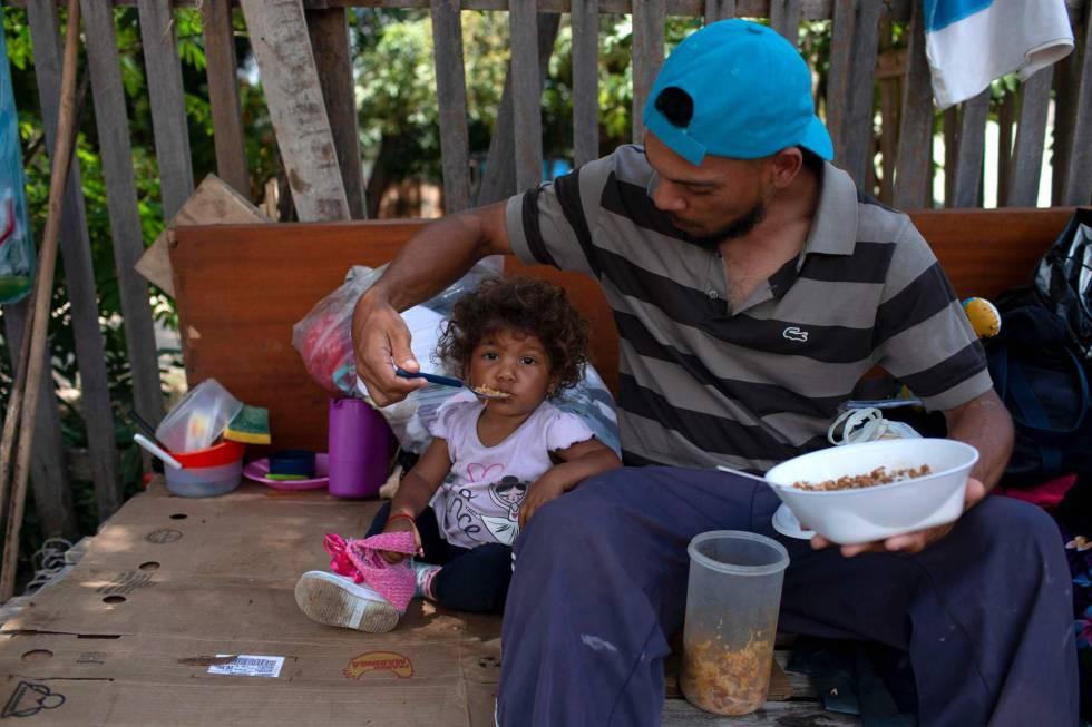 Un venezolano alimenta a su hija en el Estado de Roraima una tarde de agosto de 2018
