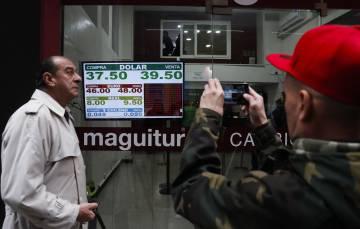 Un hombre fotografía la pizarra con la cotización del dólar, el jueves en Buenos Aires.