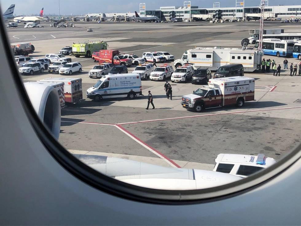Personal de emergencias este miércoles alrededor del avión de Emirates que está en cuarentena en el aeropuerto JFK de Nueva York. Fotografía tomada por un pasajero desde dentro de la aeronave.