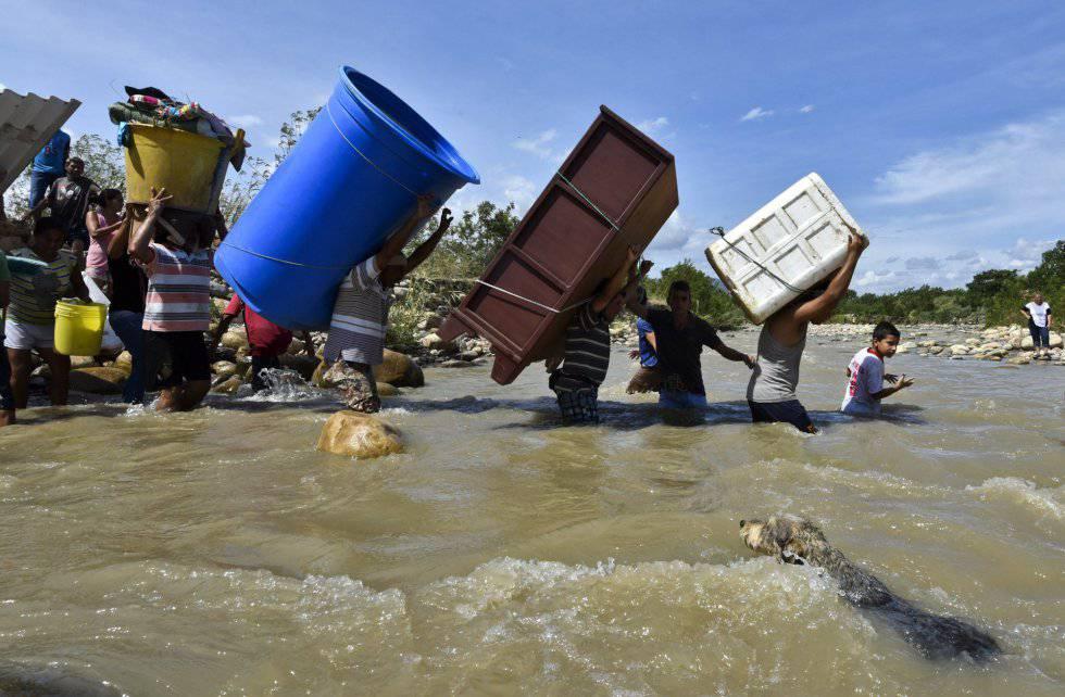 Colombianos deportados desde Venezuela cargan sus pertenencias a través del río Táchira.
