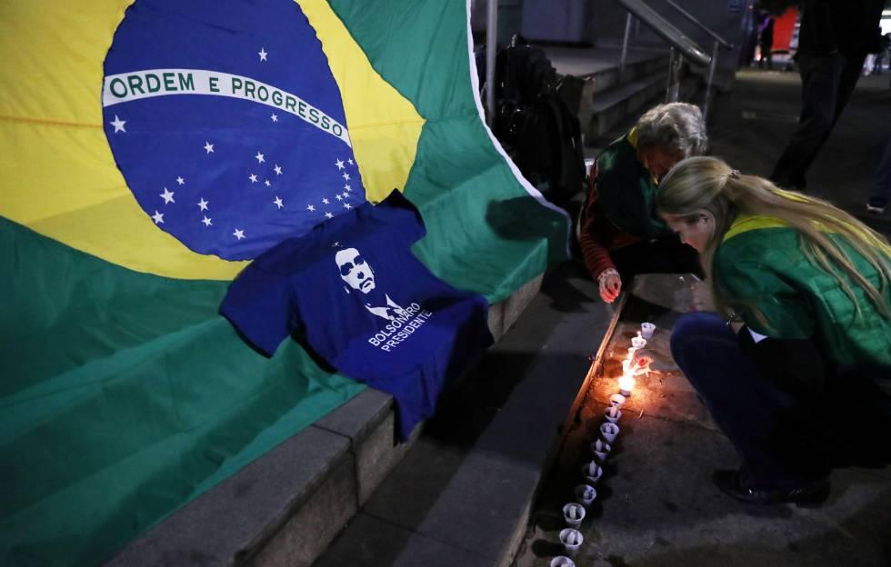 Una mujer prende una vela en una vigilia por la salud de Jair Bolsonaro