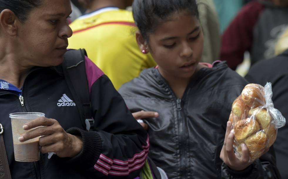 Migrantes venezolanos reciben una donación de comida en un campamento improvisado en Bogotá, Colombia.
