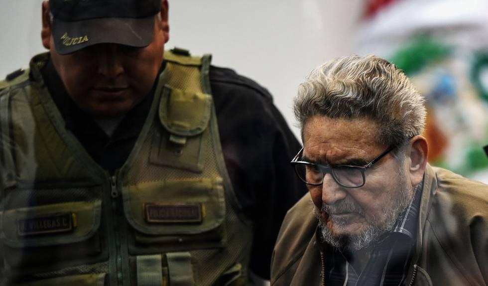 Abimael Guzmán es escoltado por un oficial de policía a su llegada a Lima.