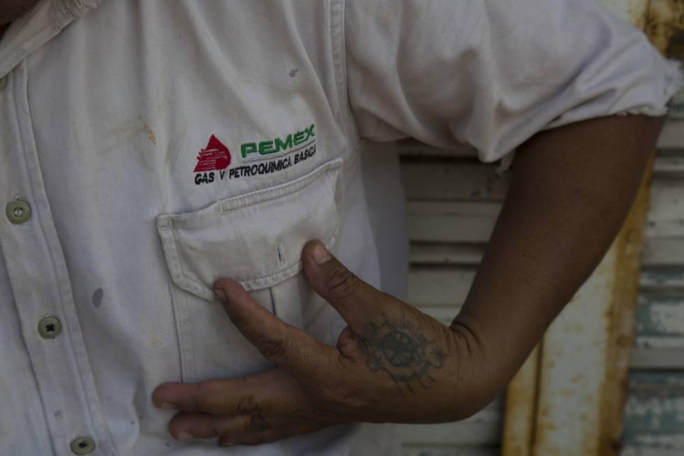 Un hombre muestra su camisa de Pemex.