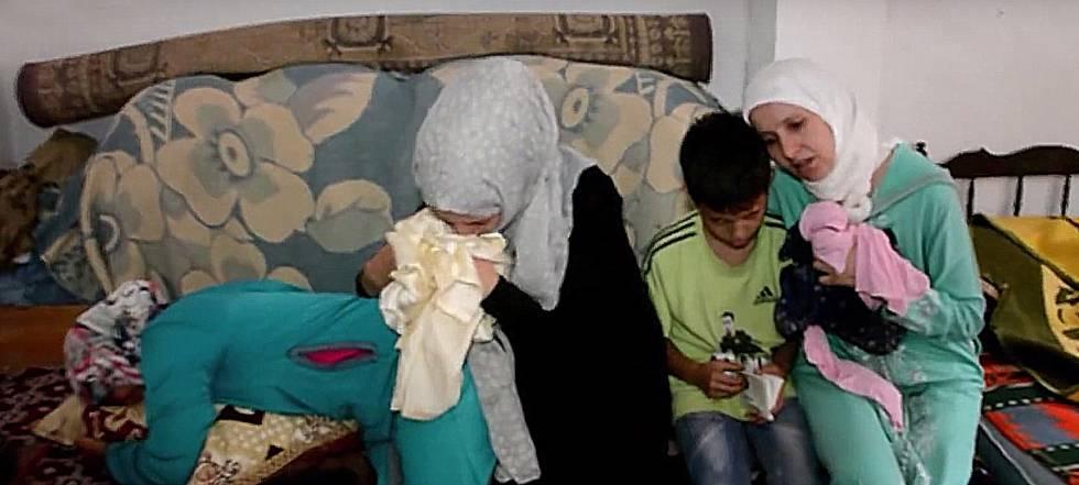 La madre de Hayat (derecha), la joven muerta por disparos de la Marina Real marroquí cuando intentaba llegar a España en una lancha, junto a tres de sus hijos   © Chouf TV