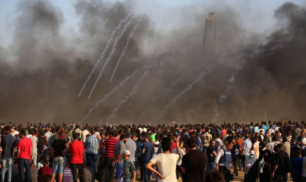 Manifestantes palestinos reaccionan al lanzamiento de gases lacrimógenos.