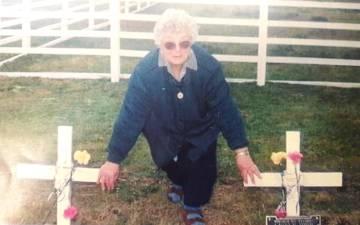 Elda posa junto a la tumba de su hijo en Malvinas, en 1998.