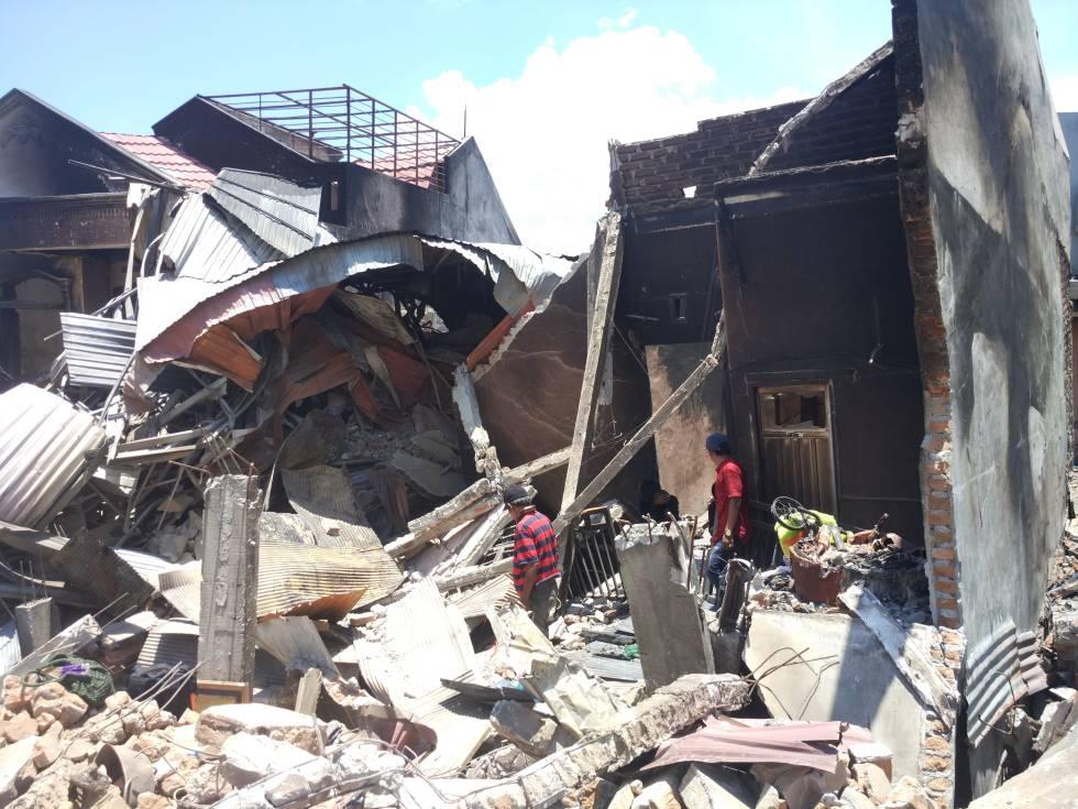 Ambo Pawe y sus dos hijos rebuscan entre las ruinas de su vivienda en el barrio de Balaroa (Palu).