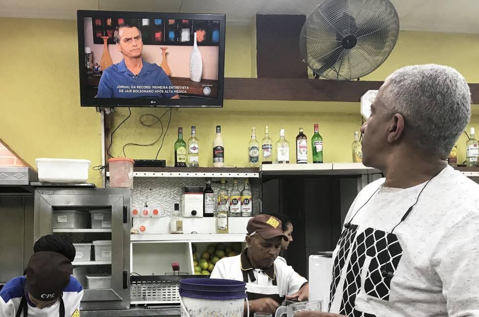 Un hombre sigue la entrevista con Jair Bolsonaro en televisión en un bar de São Paulo