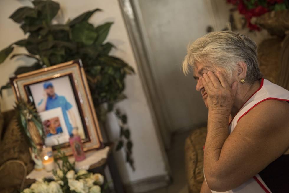 María del Transito llora frente a una foto de su hijo y su nieto en el interior de su vivienda.