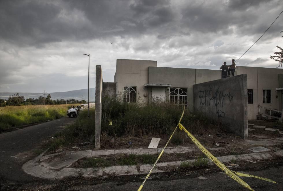 Jóvenes se asoman a observar las labores del forense en una fosa clandestina que fue descubierta en las periferias de la ciudad con cuatro cadáveres.
