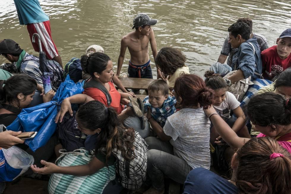 Mujeres y niños suben a una balsa para cruzar el río Suchiate.