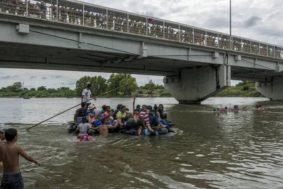 Un grupo de migrantes cruzan en balsa el río Suchiate para llegar a México.
