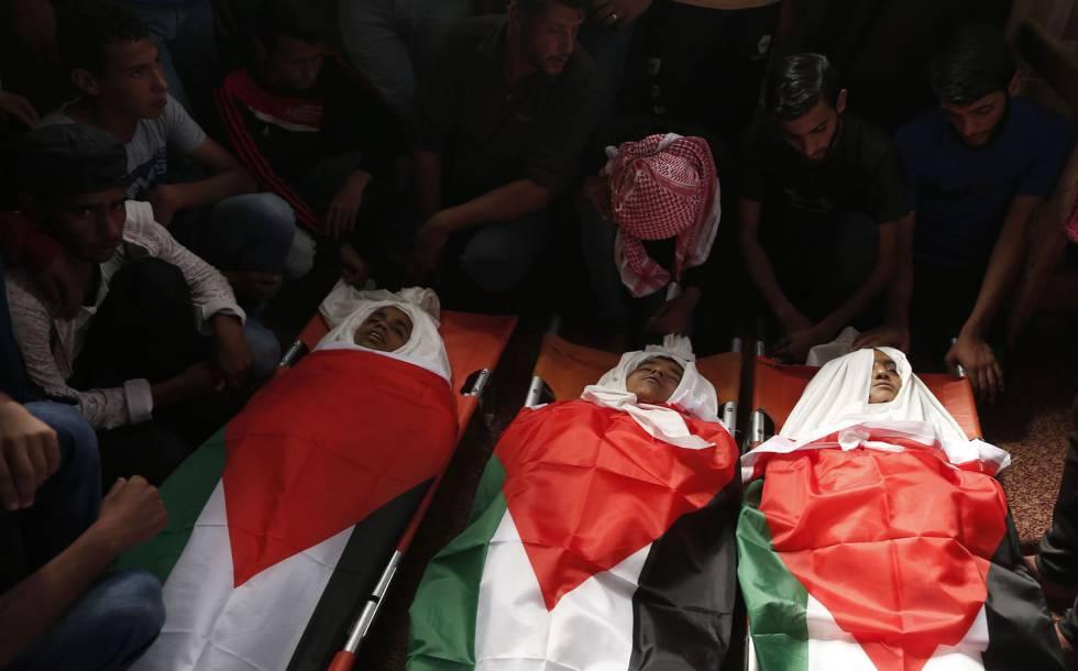 Los cadáveres de los tres menores muertos en un ataque israelí, en su funeral el lunes en Gaza.