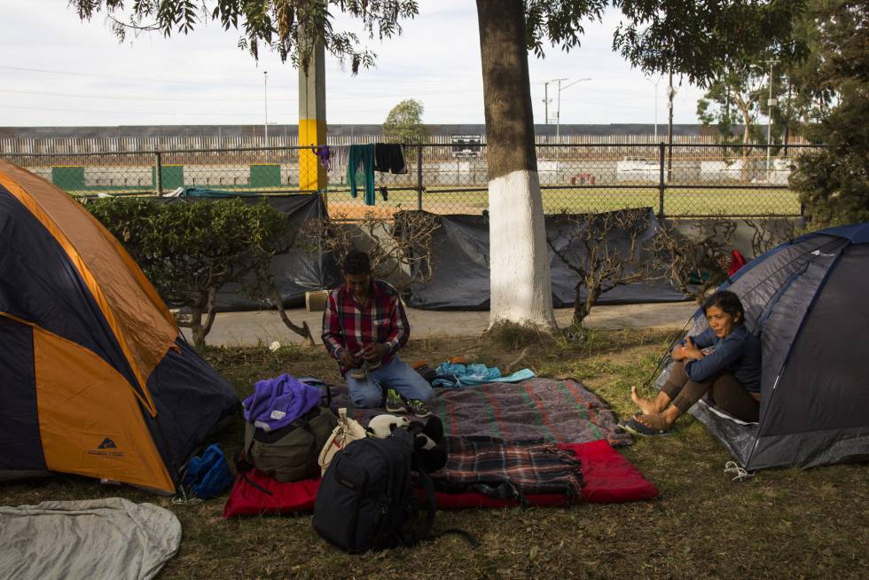 Migrantes acampan en el albergue temporal para la caravana en Tijuana. Al fondo, la valla fronteriza entre México y Estados Unidos.