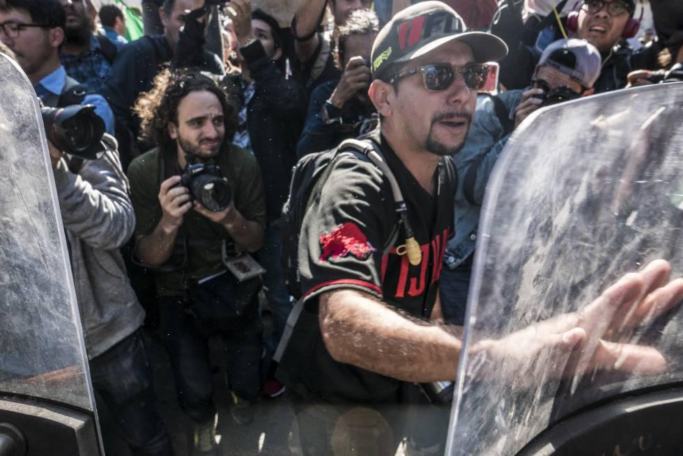 Un manifestante choca con la policía local al intentar ingresar al albergue donde pernocta la caravana de hondureños.