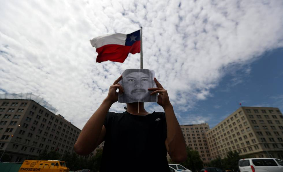 Un manifestante tapa su rostro con una foto del mapuche Camilo Catrillanca durante una protesta en Santiago, el 20 de diciembre.