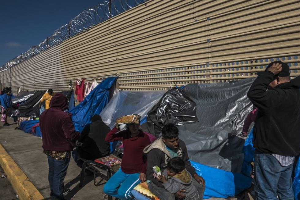 Un grupo de migrantes aguarda en un campamento improvisado frente al muro fronterizo en San Luis Río Colorado, en Sonora.