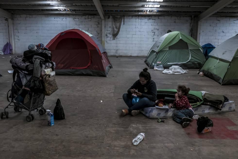 Claudia Hernández, hondureña de 29 años, junto a su hija Angelina Julieth, en una bodega en Tijuana donde convive con otros migrantes.
