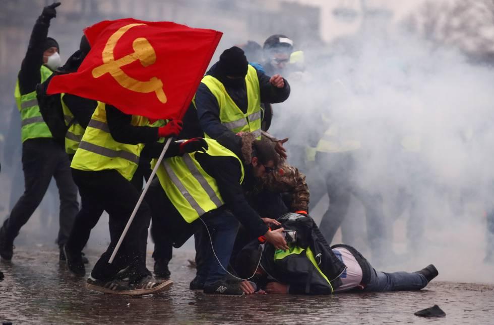 Unos 'chalecos amarillos' ayudan a un herido por el cañón de agua durante la protesta, cerca del Arco del Triunfo.